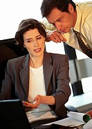 Businessman and businesswoman looking at laptop computer