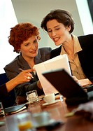 Two businesswomen sitting, looking at document