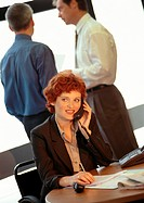 Businesswoman sitting, using phone, two businessmen in background