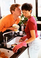 Woman washing dishes, man leaning over counter to kiss her