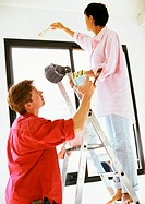 Woman painting wall, man holding ladder and paint can