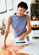 Woman looking away with head tilted, ironing clothes, waist up