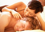 Couple lying in bed, woman touching man's ear