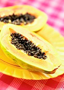 Two papaya halves on yellow plate, close-up