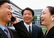 Three businesspeople laughing, one holding cell phone