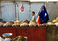 China, Xinjiang, Turpan, man behind stall in open air market