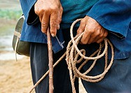 China, peasant holding rope and wood stick, mid-section, close-up