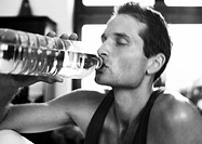 Man drinking from bottle, close-up, b&w