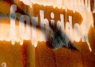 'Forbidden' text in white letters on wall, painted over, close-up