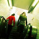 Young women going up escalator, rear view