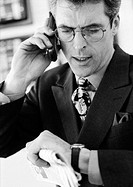 Businessman talking on cellular phone, checking time, head and shoulders, b&w