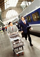 Businessmen running on train platform, blurred