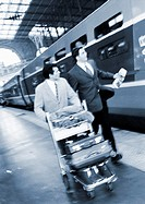 Businessmen walking next to train on platform, b&amp;w