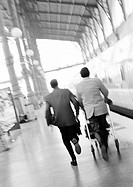 Businessmen hurrying on train platform, blurred, rear view