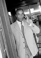 Businessman using cell phone in doorway, b&amp;w