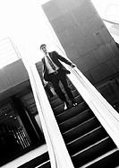 Businessman going down escalator, b&amp;w