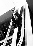 Businessman going down escalator, looking down, b&amp;w