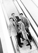 Group of business people on moving walkway smiling at camera, business woman in front on cell phone, b&w