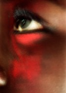 Woman´s eye looking up with red make-up on face, close-up, blurred
