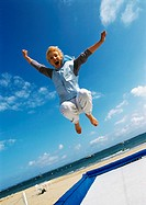 Mature woman jumping on trampoline at beach