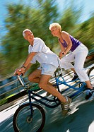 Mature man and woman riding together on tandem bike, side view, blurred