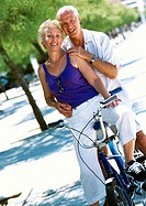 Mature man and woman posing on stationary bike, portrait