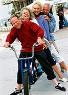 Mature men and women on stationary tandem bike, portrait