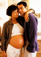 Pregnant woman standing with arm around man's shoulders, portrait