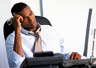 Businessman sitting at desk with eyes closed