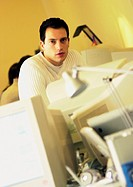 Man behind computers in office, portrait