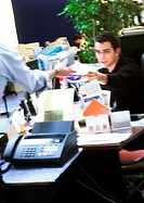 In office, man handing document to second person, blurred