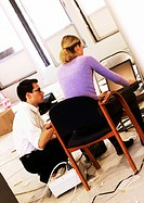Man and woman working on laptop computer on chair