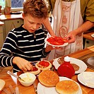 Child garnishing hamburgers, adult holding plate of tomato slices
