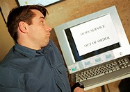 Man looking at computer screen with 'out of order' sign on screen