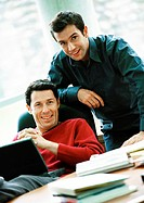 Businessmen smiling, one with laptop on lap, portrait