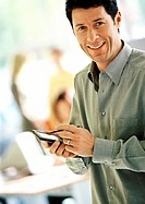 Businessman using pocket computer, smiling, portrait