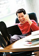 Man with laptop on lap and feet on desk, smiling