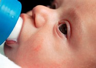 Baby's face, drinking from bottle, close-up