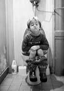 Little girl sitting on toilet, b&w