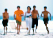 Adults running on beach, blurred