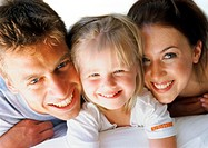 Little girl lying between parents, smiling, close-up