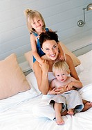 Mother and children on bed