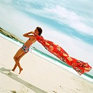 Girl in swimsuit on beach holding sarong in wind