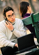 Man sitting on park bench with cell phone and laptop computer, woman sitting on other side of bench