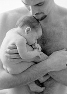 Father holding sleeping infant against bare chest, b&w