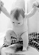 Infant standing on father's bare chest, b&w