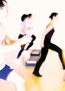 People doing step aerobics, side view, blurred