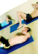 People doing sit-ups on mats, blurred