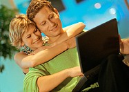 Couple smiling, man using laptop, woman with arms around man