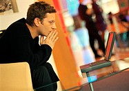 Man using laptop, hands in front of mouth, side view